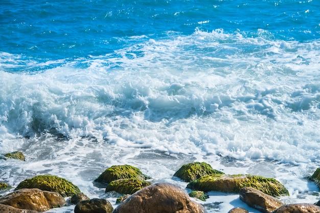 Морское побережье с камнями, серфинг волна на фоне