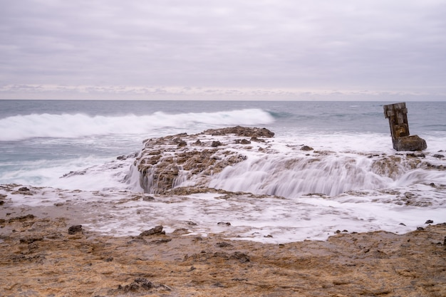 The sea crashing against the rocks at the chocolatera in salinas, ecuador