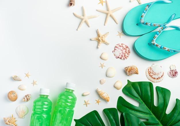 Морской стол с ракушками и морскими звездами, шлепанцы, тропический лист и освежающий напиток на светлой стене. вид сверху с копией пространства.