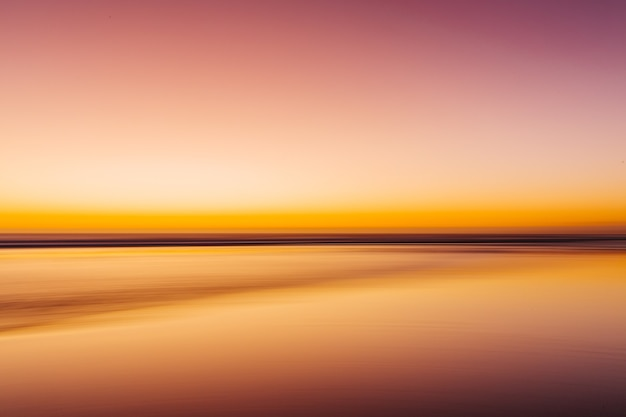 Sea during a colorful sunset with a motion effect - a cool picture for wallpapers and backgrounds
