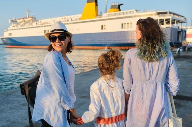 Семейный отдых на море, мать и дочери в морском порту, держась за руки, глядя на паром