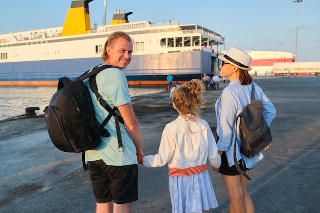 Sea family vacation, mother father and daughter child in seaport holding hands looking at the ferry
