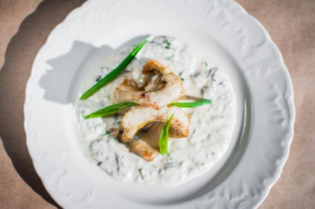 Морская рыба, тушенная в молочно-луковом соусе вкусное диетическое блюдо подается в белой тарелке