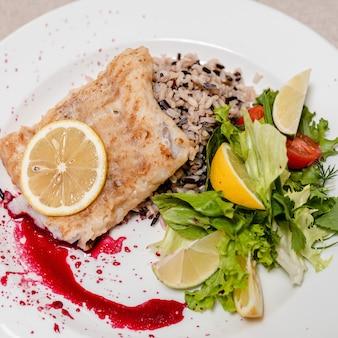Морская рыба, тушенная в молочно-луковом соусе с рисом вкусное диетическое питание подается в белой тарелке