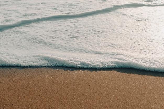 Sea foam on beach shore at sunset. wallpaper