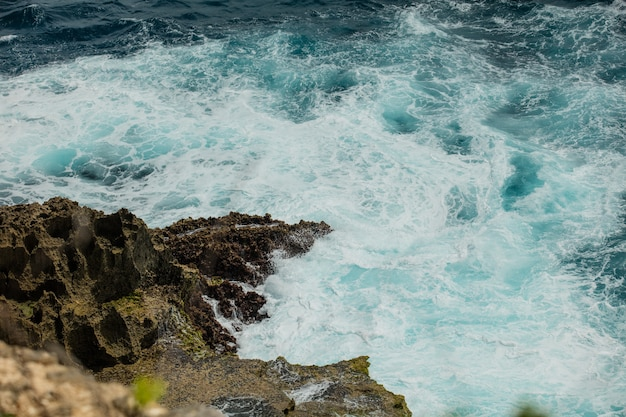 Sea foam wave running on a rocky shore top view summer background