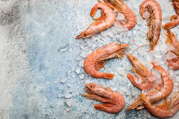 青いコピースペースの上に氷と生エビの海の食品組成フラットレイ