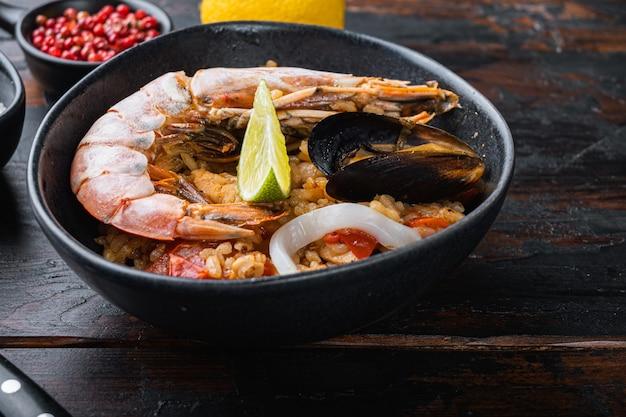 Sea food specialties paella in bowl on old dark wooden table, food photo.