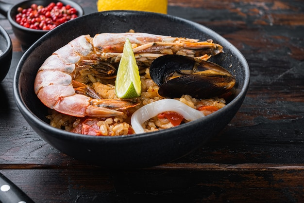 Паэлья деликатесов морепродуктов в шаре на старом темном деревянном столе, фото еды.