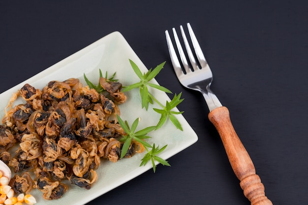 Sea food sweet dried clams on dish with fork