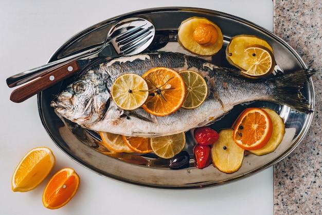맛있는 열대 과일과 채소로 구운 접시에 있는 바다 길트헤드 도미