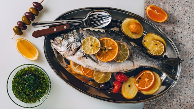 Sea gilthead bream fish on the plate baked with tasty selection of tropical fruits and vegetables
