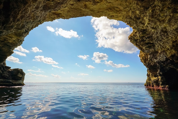 Sea grotto in the rock on a bright sunny day .
