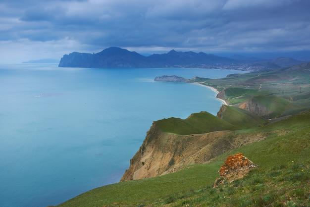 Морская гавань с голубой водой, зеленым полем и голубым небом с облаками