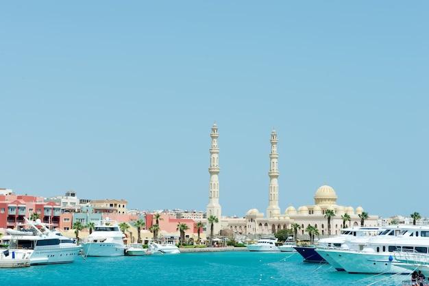주차 된 스피드 보트와 후르 가다 모스크가있는 돌 도시 제방이있는 바다 항구