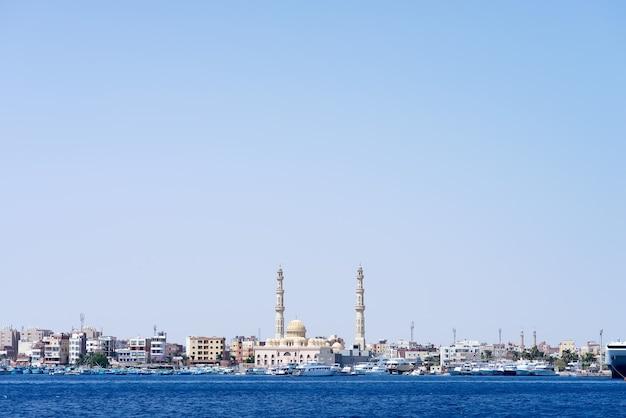 停泊中のスピードボートとハルガダモスクのある石造りの街の堤防がある海の港
