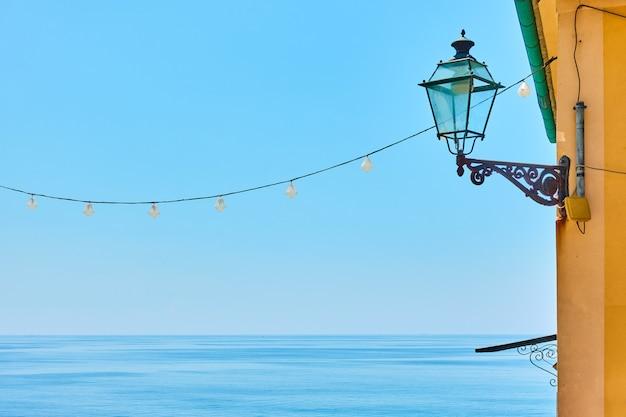 Морской горизонт, ясное голубое небо и старинный уличный фонарь на стене - фон с пространством для текста, италия