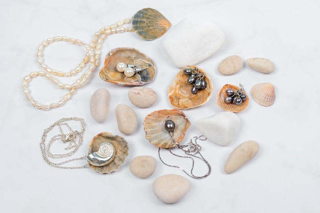 Коллекция морских украшений на светлом мраморе с ракушками и галькой