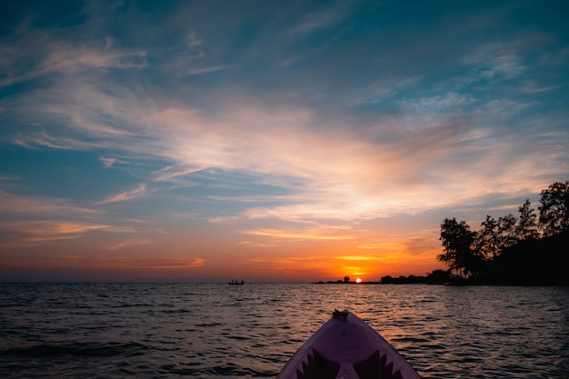 The sea kayak and silhouette of fishing boat on sunset