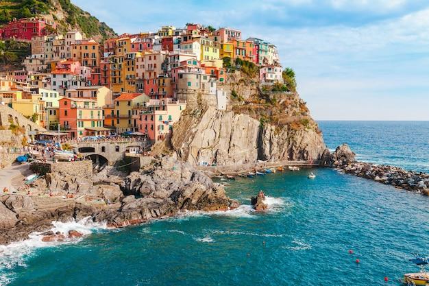 Морской пейзаж в деревне манарола, побережье италии чинкве-терре. живописный красивый городок в провинции ла специя, лигурия с традиционными домами. известное туристическое направление