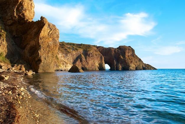 Морской пейзаж с гротом в скале Premium Фотографии