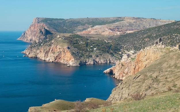Морской пейзаж со скалами и башней.
