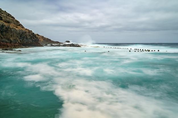 Морской пейзаж со скалами, волнами и облачным небом. фотография с длинной выдержкой. испания, европа,