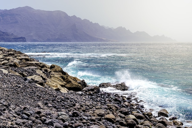 Sea landscape with rocky beach and waves breaking on the coast, distant mountains with high cliffs. europe,
