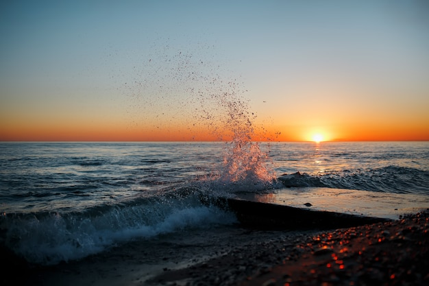 Sea landscape with waves on the beach against sunset