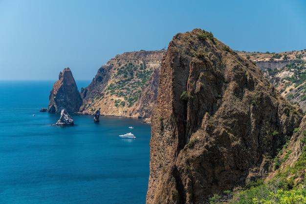 ヨットと岩の多い海岸線のある海の風景。岩の多い海岸を背景にした海のヨット。