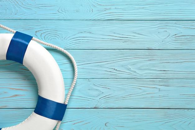 Спасательный круг на синем деревянном