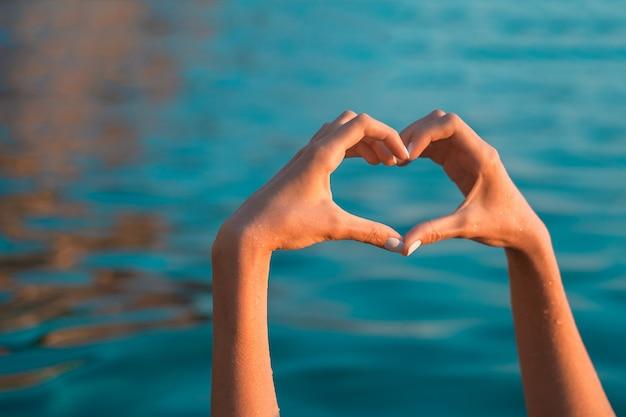 Sea love. hands in heart shape at blue sea