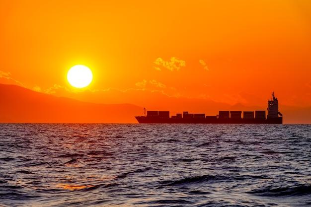 海岸近くの海。明るいオレンジ色の夕日。大きな太陽とコンテナ船のシルエット