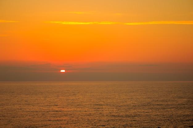 夕日の背景に海。