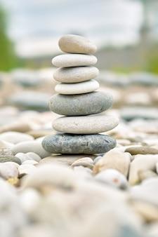 庭にそびえる海の小石。積み重ねられたバランスジャックストーンのクローズアップビュー(ソフトフォーカス写真)