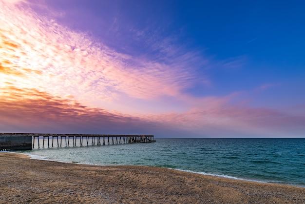 日没時の海の桟橋、色とりどりの空