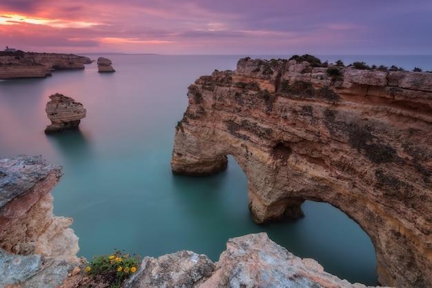 Море розовый закат на пляже маринья. португалия алгарве.