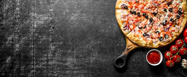 Sea pizza and tomato sauce in bowl. on dark rustic background