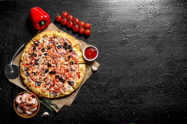 Sea pizza with bell peppers, tomatoes and shrimp. on black rustic background