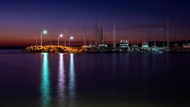 여러 정박 된 보트, 그리스의 가로등 기둥이있는에게 해 연안의 밤 바다 포트