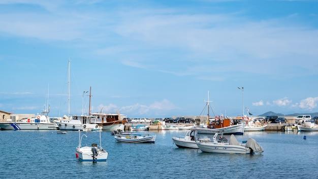 Sea port, moored boats and yachts on aegean sea, multiple parked cars, ierissos, greece