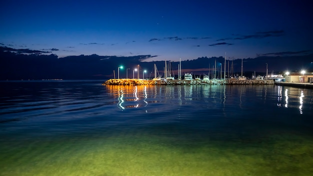 Sea port at night at aegean sea coast with multiple moored boats, lampposts in greece