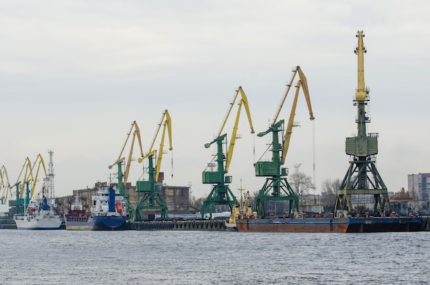 Sea port with cranes, ships at the pier for loading goods.