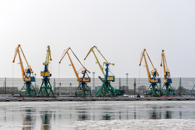 Sea port with rows of large industrial cranes to lift goods off the decks