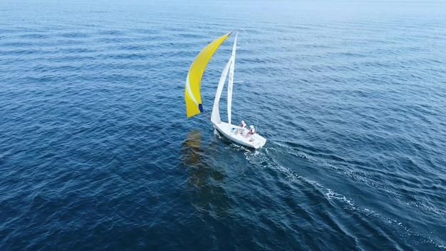 海のレガッタ。黄色い帆の美しい白いヨットが青い海を航行します。