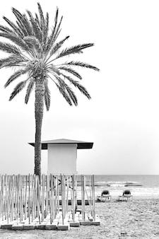 Морской курортный пляж в низкий сезон. черное и белое