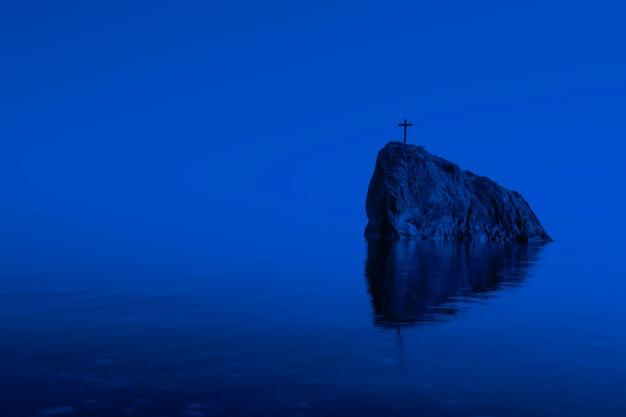 달빛에 밤에 상단에 십자가와 해초가 있는 바다 바위