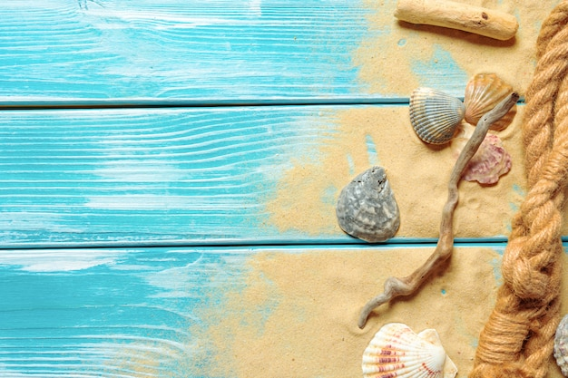 Sea rope with many different sea shells on the sea sand on a blue wooden background. top view