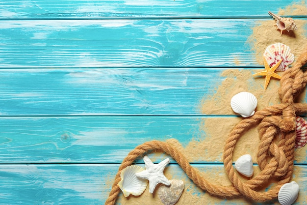 Sea rope with many different sea shells on the sea sand on a blue wooden background with copyspace. top view