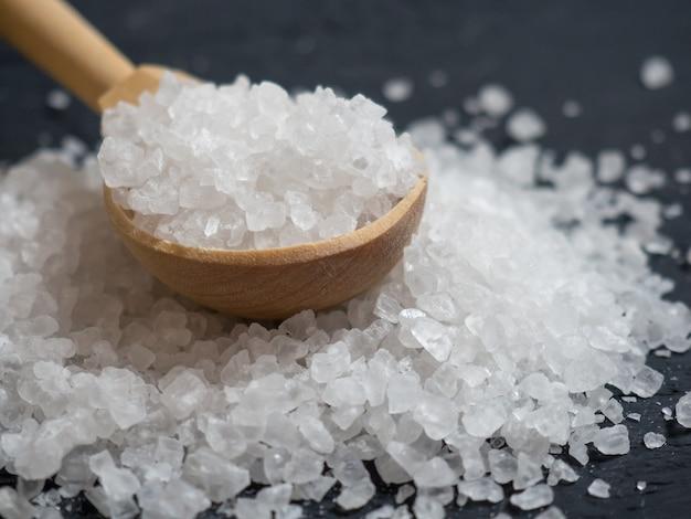 海の塩、古い木製の背景のクローズアップに木のスプーンで海の塩の山